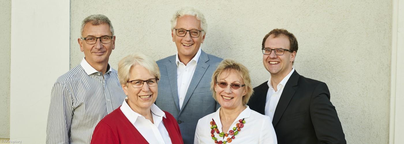 Team des Regionalbischofs in Augsburg vor grauer Wand